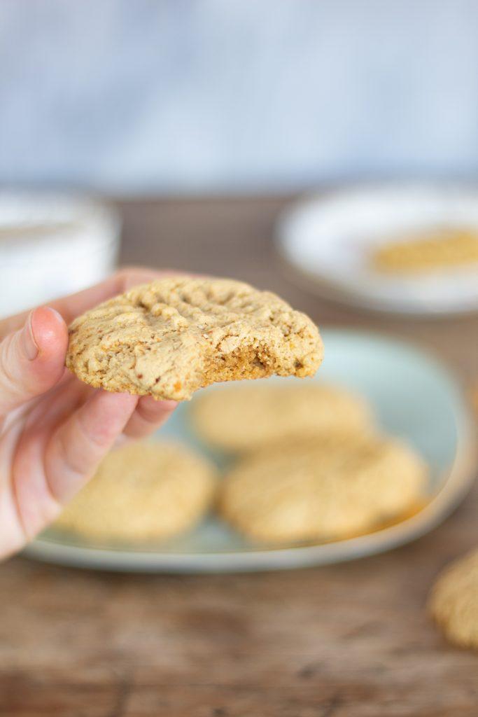 Una galleta sin harina mordida sostenida por una mano